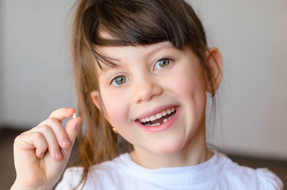 Beautiful smiling preschool girl holds in hand her first dropped baby tooth Dental implants Calgary NW